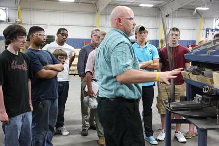 Doug Nolan, Plant Manager, speaks to students about processes in manufacturing.